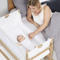 Snuzpod Bedside Cot Co Sleeper in a natural wood finish and breathable mesh sides features a lightweight lift-off bassinet